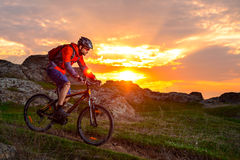 Cyclist Riding Mountain Bike on the Spring Rocky Trail at Beautiful Sunset. Extreme Sports and Adventure Concept. Stock Images
