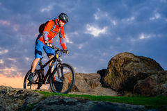 Cyclist Riding Mountain Bike on the Spring Rocky Trail at Beautiful Sunset. Extreme Sports and Adventure Concept. Royalty Free Stock Photos