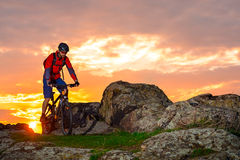 Cyclist Riding Mountain Bike on the Spring Rocky Trail at Beautiful Sunset. Extreme Sports and Adventure Concept. Stock Photo