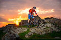 Cyclist Riding Mountain Bike on the Spring Rocky Trail at Beautiful Sunset. Extreme Sports and Adventure Concept. Royalty Free Stock Image