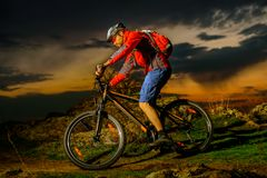Cyclist Riding Mountain Bike on Spring Rocky Trail at Beautiful Sunset. Extreme Sports and Adventure Concept. stock photo