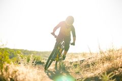 Cyclist Riding the Mountain Bike on the Summer Rocky Trail at the Evening. Extreme Sport and Enduro Cycling Concept. Stock Photography