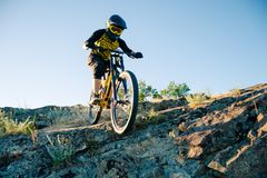 Cyclist Riding the Mountain Bike on the Summer Rocky Trail at the Evening. Extreme Sport and Enduro Cycling Concept. Professional Cyclist Riding the Downhill royalty free stock photos