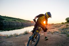 Cyclist Riding the Mountain Bike on the Summer Rocky Trail at the Evening. Extreme Sport and Enduro Cycling Concept. Royalty Free Stock Images