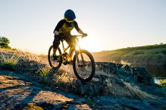 Cyclist Riding the Mountain Bike on the Summer Rocky Trail at the Evening. Extreme Sport and Enduro Cycling Concept. Professional Cyclist Riding the Downhill royalty free stock photo