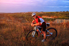Cyclist riding mountain bike on trail at evening. Royalty Free Stock Photos