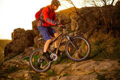 Cyclist Riding Mountain Bike Up Rocky Hill on the Spring Trail at Sunset. Extreme Sports Concept. Royalty Free Stock Photography