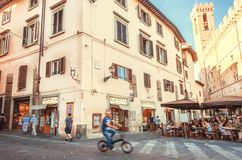 Cyclist riding past restaurants with eating people on street off the ancient Tuscany city. FLORENCE, ITALY - SEPT 24: Cyclist riding past restaurants with eating royalty free stock photos