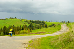 Cyclist riding on the road. Green Hills. Winding road. A cyclist rides to the goal Stock Photography