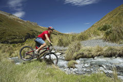 Cyclist Riding Through Rocky Field. Side view of a male cyclist riding through rocky field stock photos