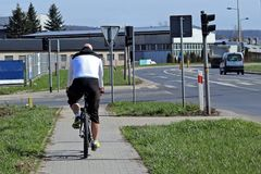 The cyclist is riding by the sidewalk near the road on which the cars are going. Transport city system. Ecological type of transpo Royalty Free Stock Images