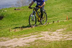 Cyclist riding on track. Closeup of male cyclist riding on green grass track Royalty Free Stock Images
