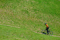 Cyclist Riding Up the Green Hill Royalty Free Stock Photography
