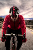 Cyclist on the road. Cyclist on road bike through a asphalt road in the mountains and blue sky with clouds stock images