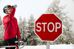 Cyclist on the road. Cyclist on road bike near a stop sign in the mountains with snow Stock Photo