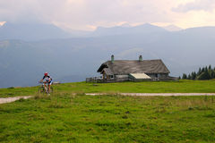 A cyclist on the road between the fields with view on the mountains and a house in the clouds. Travel to Sankt-Wolfgang, Austria. A cyclist on the road between Royalty Free Stock Photography