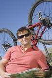 Cyclist With Roadmap Lying In Front Of Bicycle Upside Down Royalty Free Stock Photos