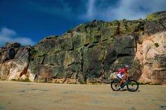 Cyclist on roadway passing through rocky landscape. Serra da Estrela, Portugal, July 14, 2018. Cyclist on roadway passing through rocky landscape, at the stock images