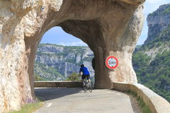 Cyclist through rocks D942, gorges de la Nesque, France Royalty Free Stock Photo