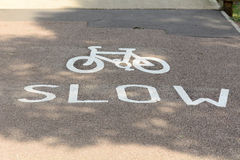 Cyclists slow sign. Cyclists painted go slow sign on pathway Royalty Free Stock Images