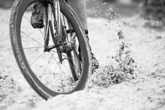 Cyclist in Sand. Bicycle tires kicking up sand royalty free stock photography