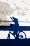 Cyclist shadow. On tour on the snowy surface Royalty Free Stock Image