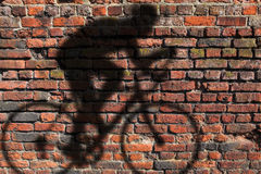 Cyclist shadow on wall Stock Images