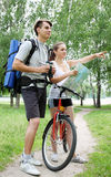 Cyclist shows the way the hiker. Traveler asks for directions from a cyclist Royalty Free Stock Photo