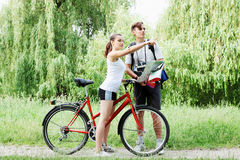 Cyclist shows the way the traveler. Traveler asks for directions from a cyclist Royalty Free Stock Photo