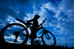 Cyclist silhouette on a blue sky Stock Image