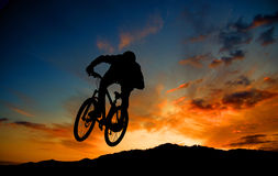 Cyclist silhouetted at sunset. Rear view of silhouetted mountain cyclist in mid air with colorful sunset background Stock Photos
