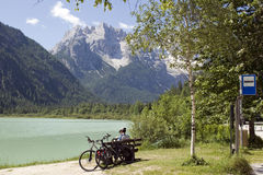 Cyclist sitting in front beautiful Dolomites vie. Lake Landro and bus stop on the road to Cortina,Italy Stock Photography