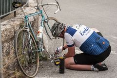 A cyclist sitting on the roadside,repairing the inner tube of hi royalty free stock photography