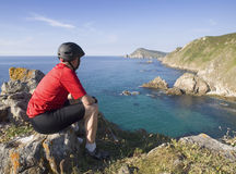 Cyclist sitting, staring at a coastal landscape Royalty Free Stock Photo