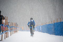 Cyclist in Snow. A cyclist competes in the snow stock photography
