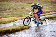 Cyclist at the speed of moving mountain river Royalty Free Stock Image