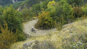Cyclist on sport bike rides on serpentine mountain road. competitions on mountainbike stock footage