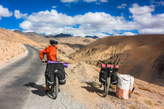 Cyclist standing on mountains road. Himalayas Royalty Free Stock Image