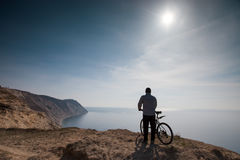 A cyclist stands on the high seashore. A cyclist stands on a beautiful high seashore Stock Photography