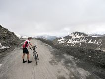 Cyclist stands next to his bicycle on top of mountain pass col de la bonette in the french alps royalty free stock images