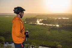 Cyclist at sunset in the mountains. A young man in a helmet and glasses drinks water from a bottle. A cyclist in an orange hoodie rides a bike along a mountain Stock Image