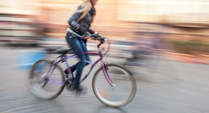 Cyclist in traffic on the city roadway Stock Images