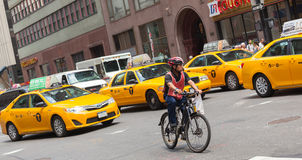 Cyclist in traffic between the yellow cabs in Manhattan, NYC. Royalty Free Stock Photo