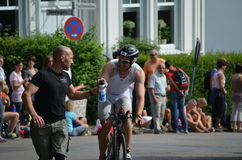 A cyclist at a triathlon receives energy drink Stock Images