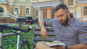Cyclist turns the page of the book on the bench. Young brunette cyclist turning the page of the book on the bench. Handsome bearded man holding some literary stock video footage