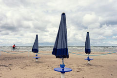 Cyclist and umbrellas on the beach of the Baltic Sea Stock Photography