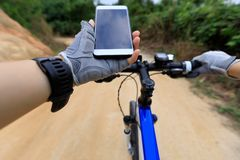 Cyclist use smartphone for navigation. Cycling mountain bike on country road Stock Photos
