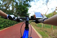 Cyclist use smartphone for navigation. When riding mountain bike on forest trail Royalty Free Stock Images