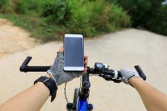 Cyclist use smartphone for navigation. In front of the Crossroads to choose the correct way Royalty Free Stock Photography