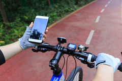Cyclist use smartphone for navigation. When riding mountain bike on forest trail Stock Image